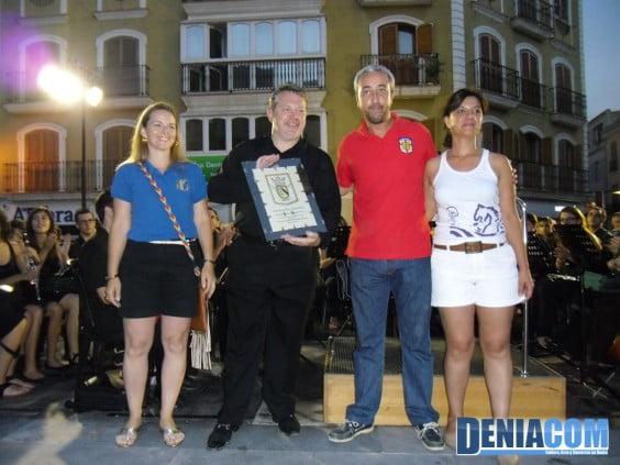 El presidente de la AMMICC entrega una placa al director de la Banda de Dénia