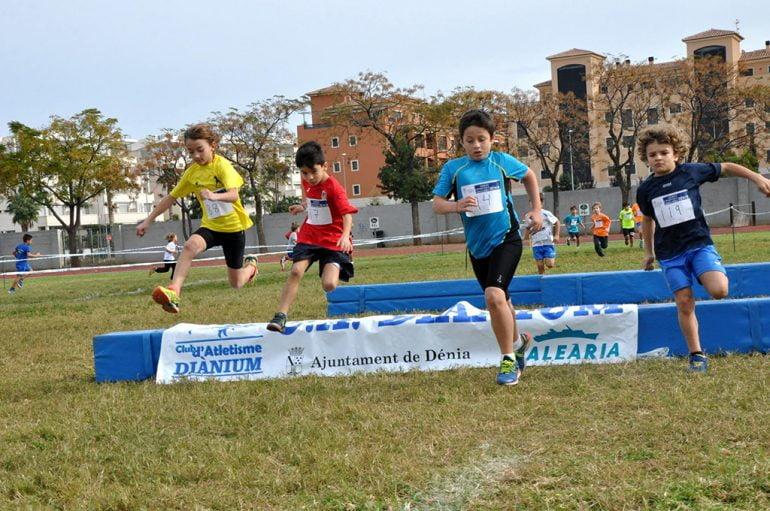 Pequeños atletas saltando un obstáculo