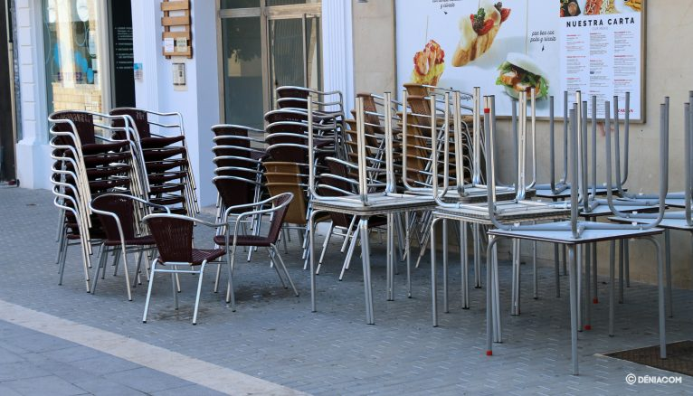 Cadires i taules apilades en un local de Dénia