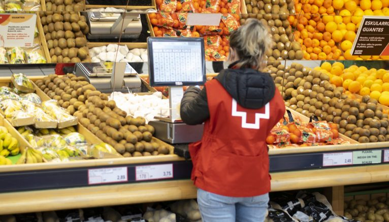 Volunteer in the fruit and vegetable section of a supermarket