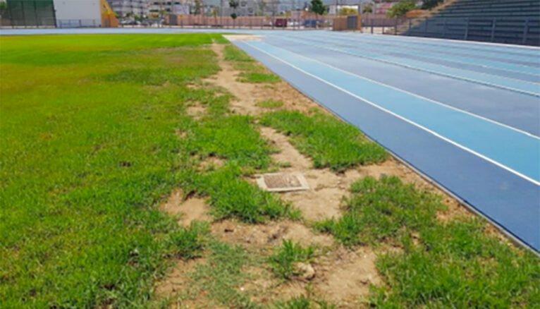 Arquetas de cemento con tapas de metal junto al campo de rugby