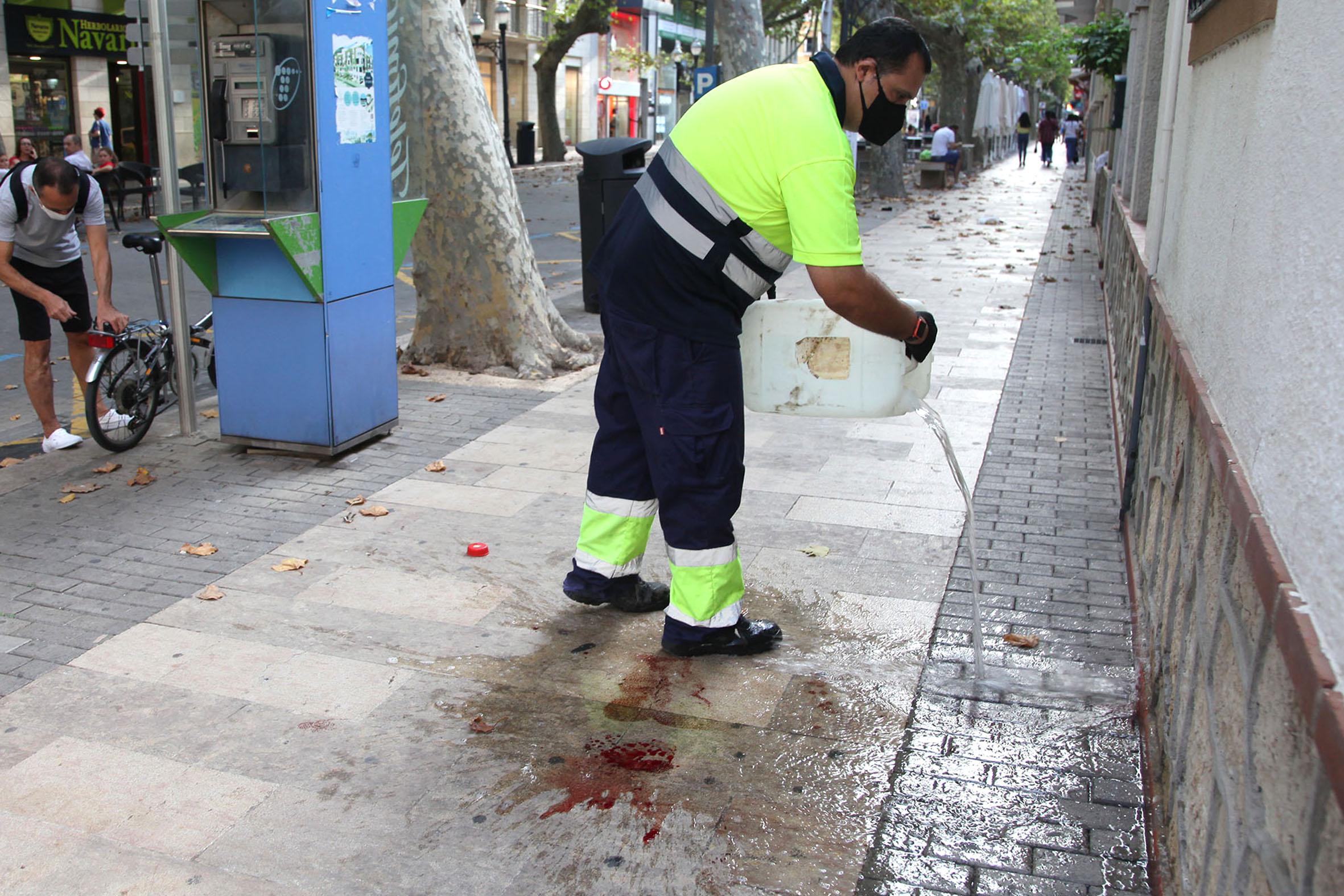 Personal de limpieza limpia la sangre de la calle