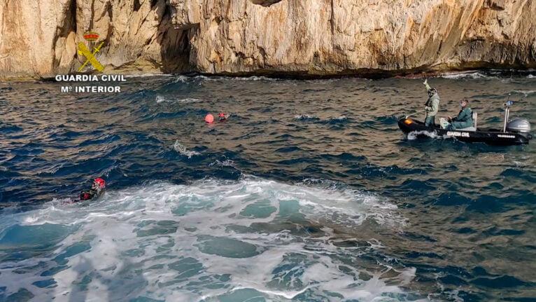 Buzos de la Guardia Civil junto a una embarcación neumática