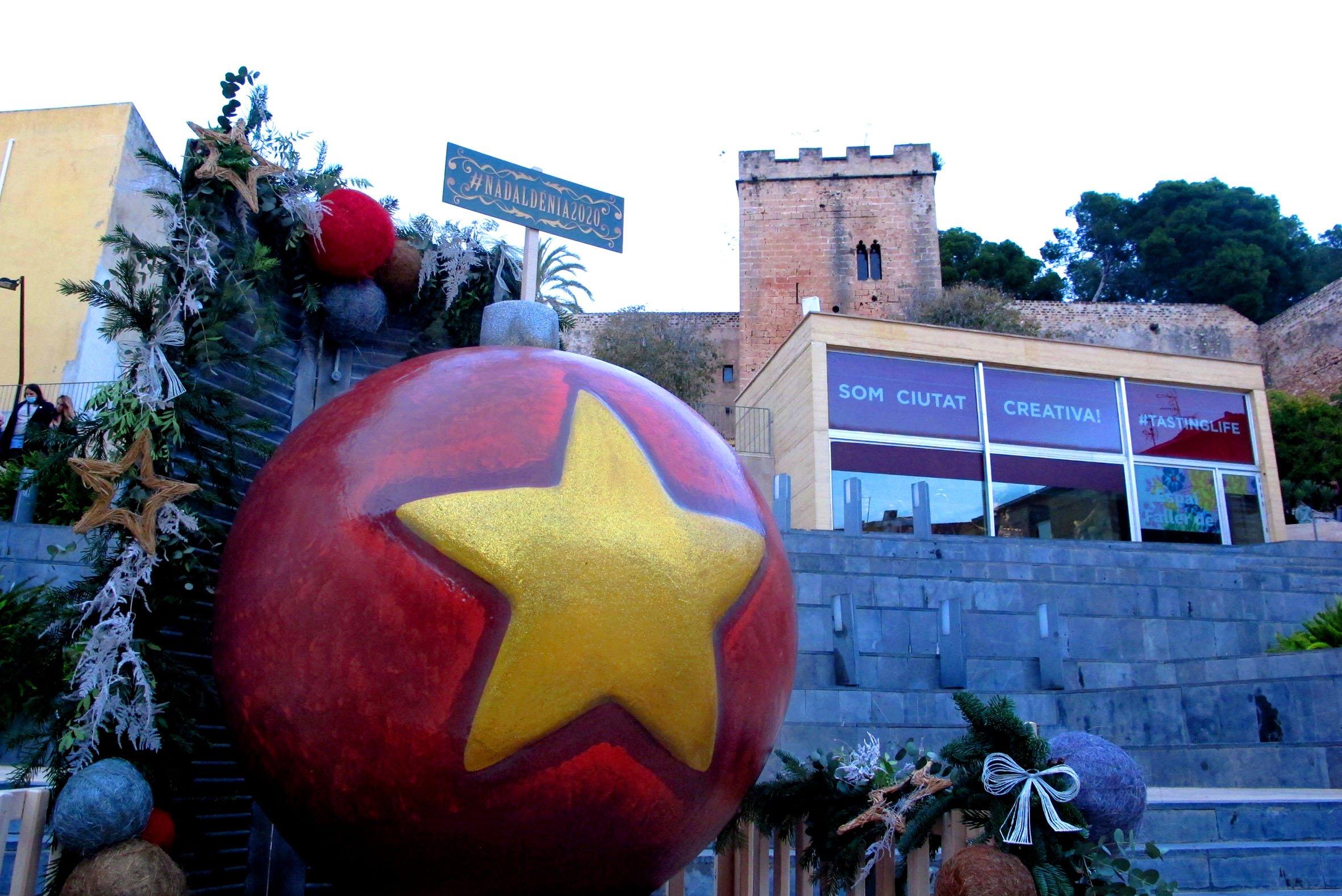 Una gran bola de árbol de Navidad luce en la Plaza del Consell