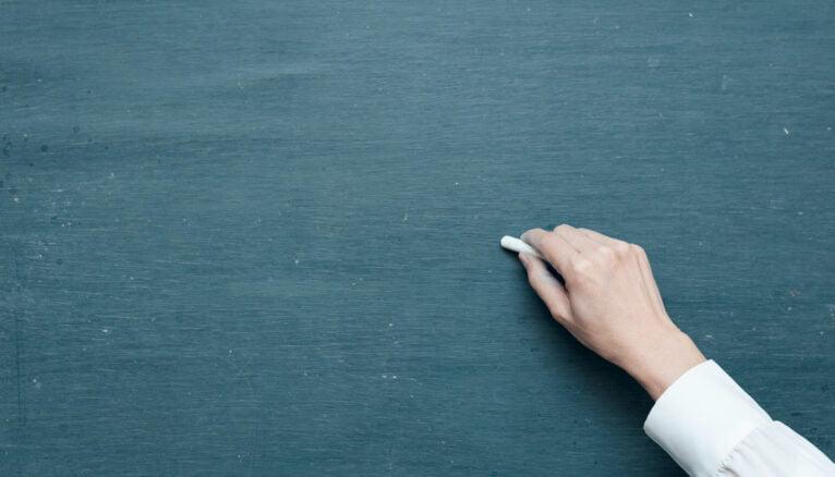 Enseignant écrit sur un tableau noir