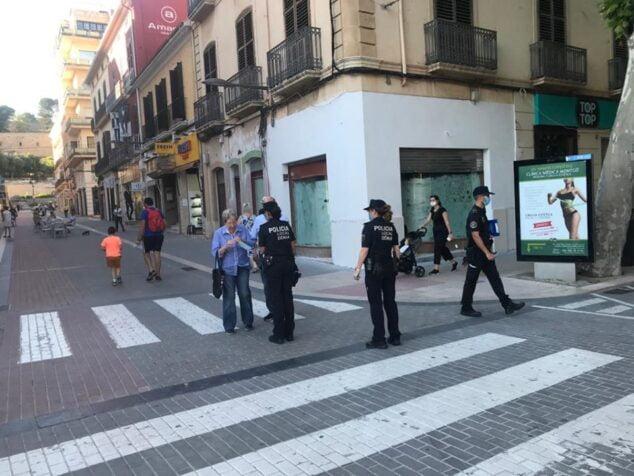 Image: Des policiers locaux distribuant des masques pendant la désescalade