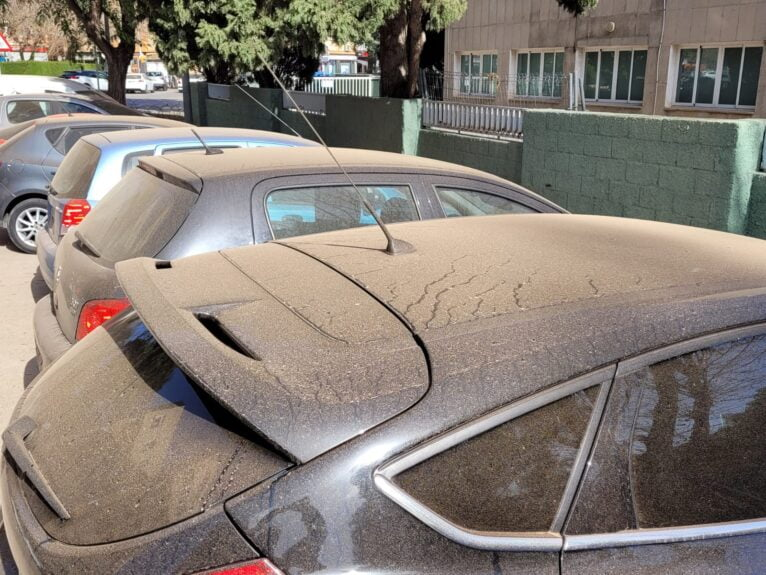 Parked vehicles soiled by sand