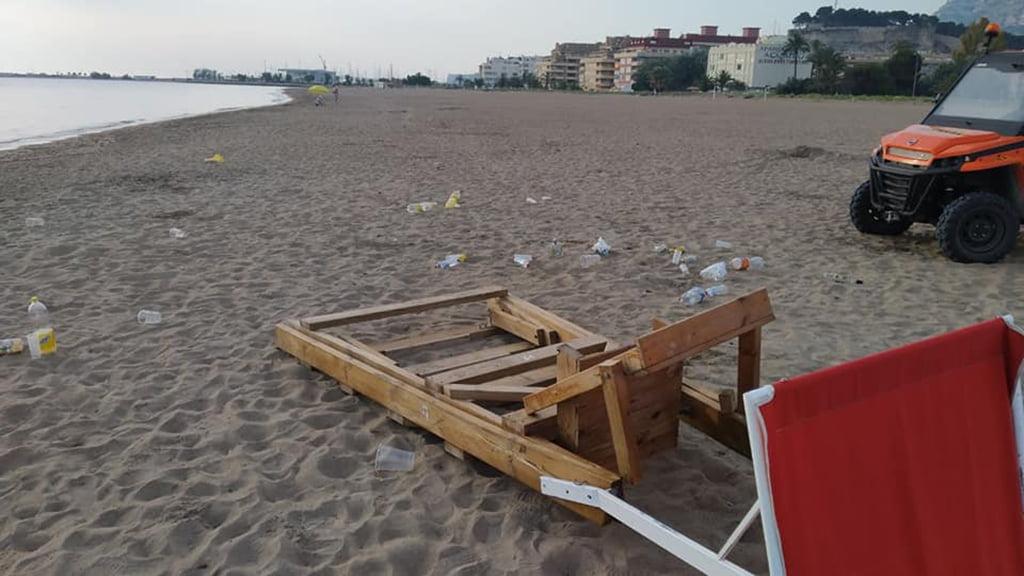 Basura y una silla de proximidad volcada en una playa de Dénia