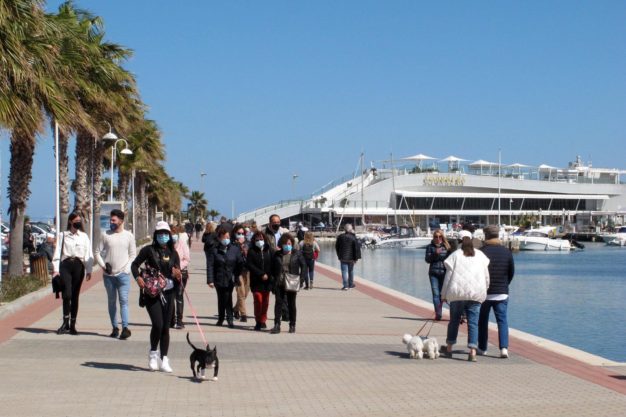 Gente paseando por el puerto de Dénia con mascarillas