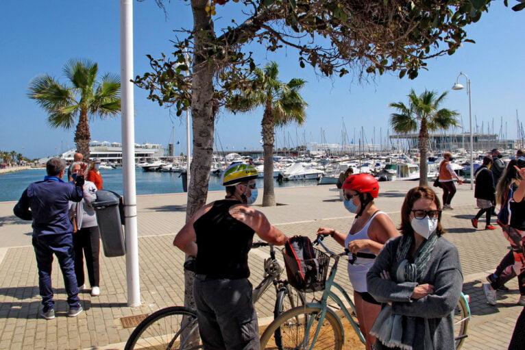 Personas paseando con mascarilla por el puerto de Dénia