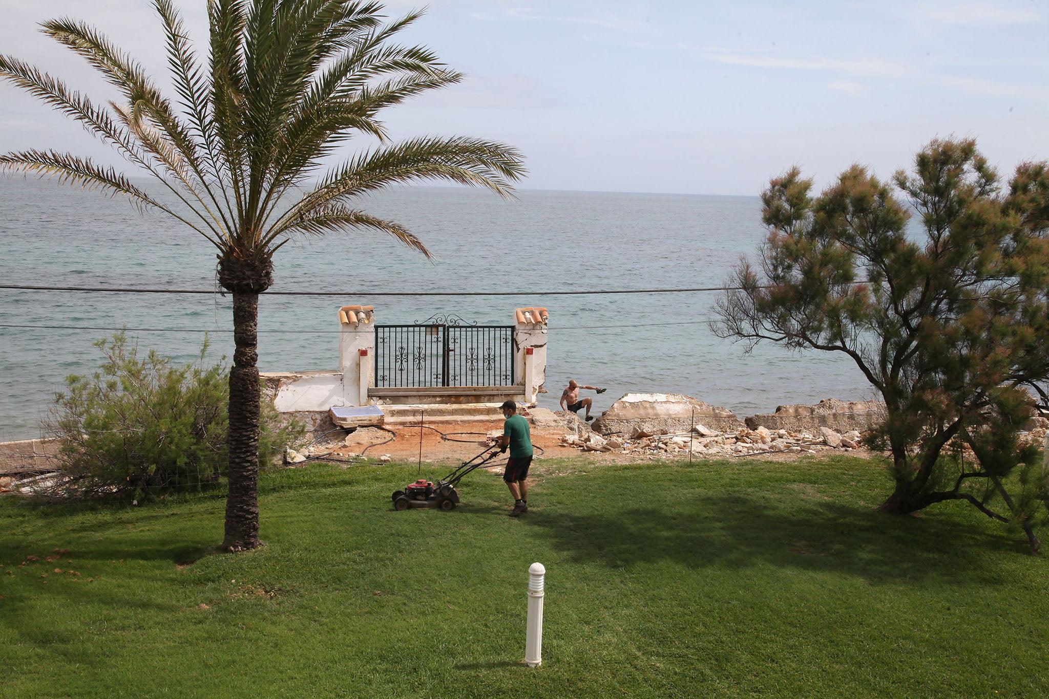 Un bañista sortea los escombros mientras a pocos metros cuidan el jardin de la propiedad