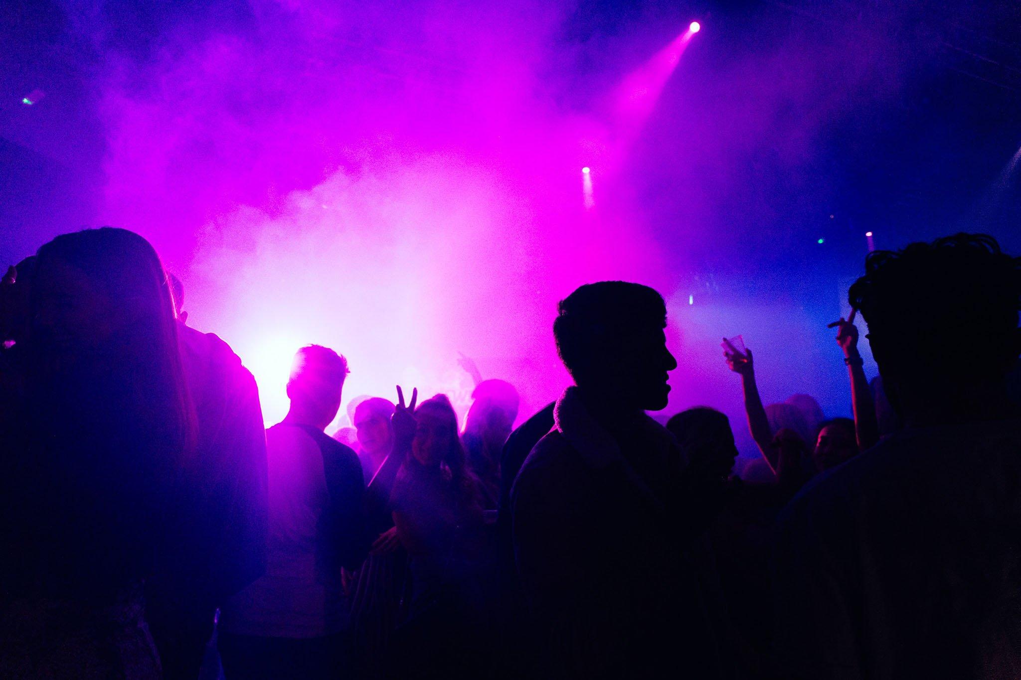 Gente joven en el interior de una discoteca bailando