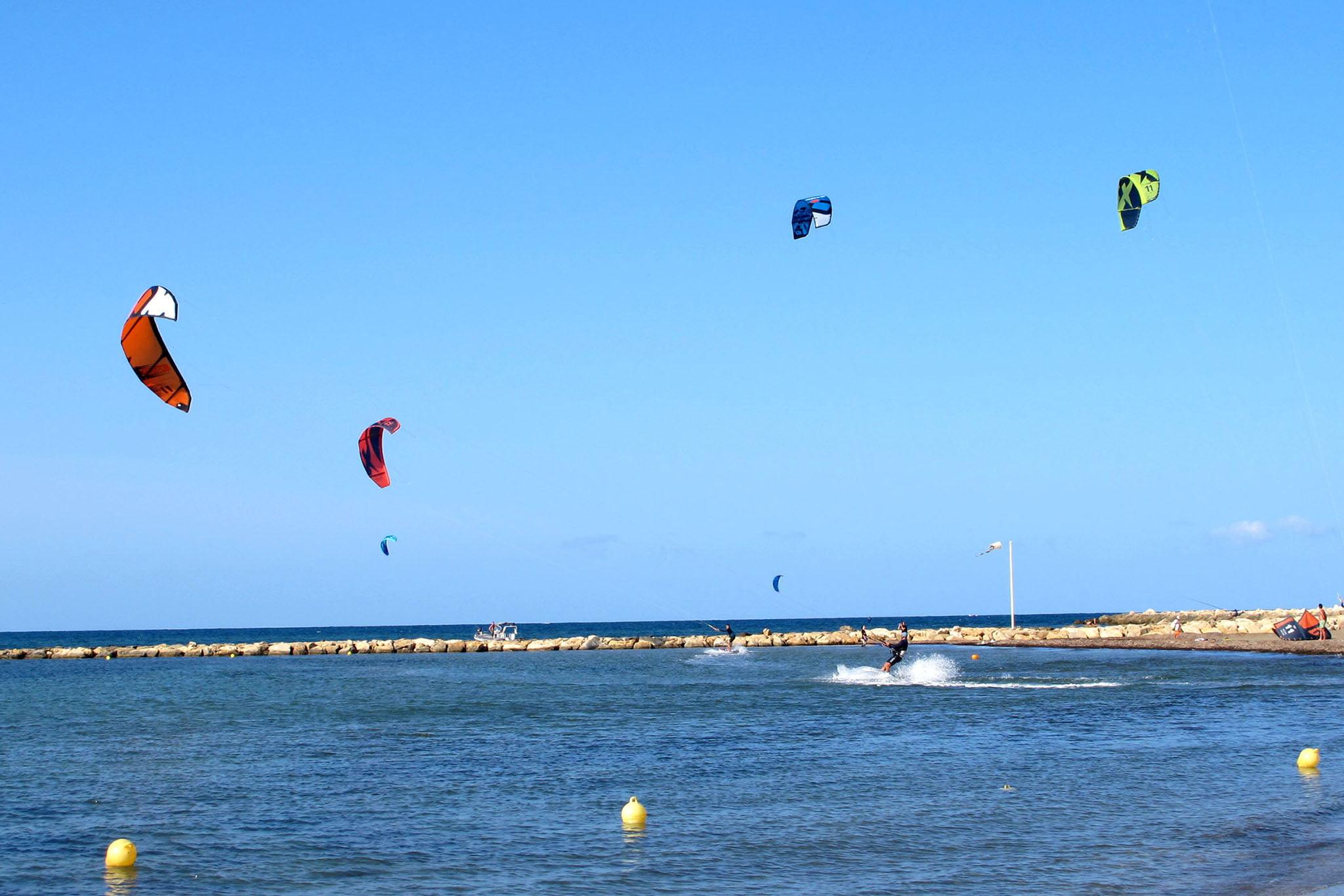Bañistas practicando kite surf en la zona habilitada de El Raset